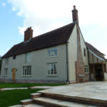 Front elevation showing the new lime render finish and the new oak Porch